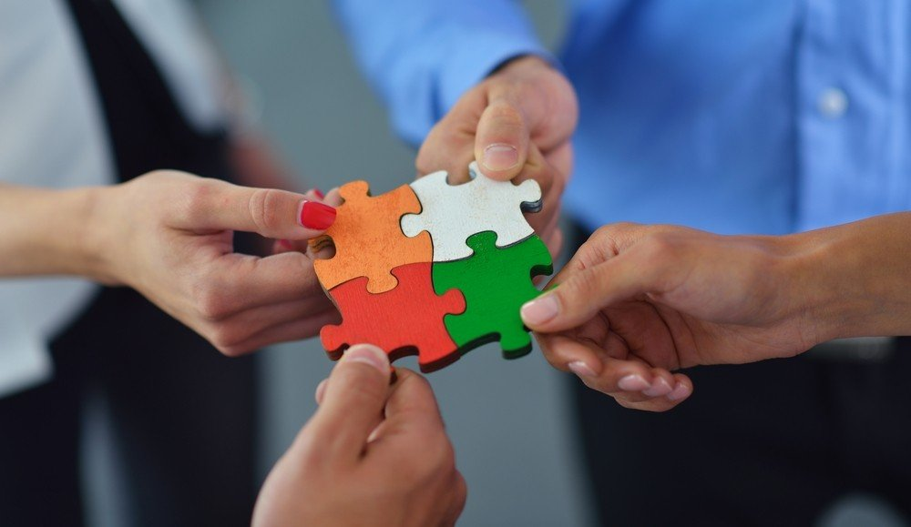 four-people-joining-jigsaw-pieces-together